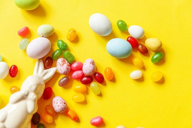Wesołych świąt wielkanocnych. przygotowanie do wakacji. wielkanocny cukierek czekoladowych jajek królik i słodyczy jellybean odizolowywający na modnym kolorze żółtym. widok z góry prosty minimalizm płasko widok z góry.