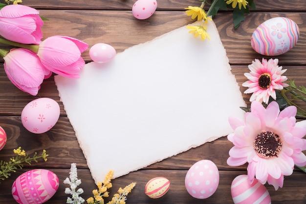 Wesołych świąt wielkanocnych różowe jaja i dekoracje kwiatowe na drewnie
