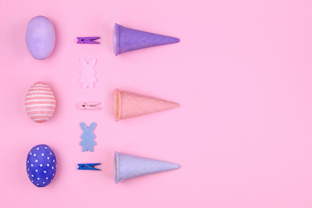 Wesołych świąt wielkanocnych. różowe, niebieskie i fioletowe pisanki, kolorowe spinacze do bielizny, rożek waflowy i sylwetka królika na różowym tle