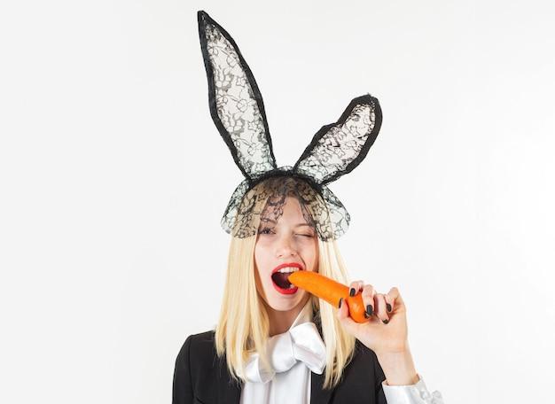 Wesołych świąt wielkanocnych. seksowny zajączek jedzący marchewkę. zmysłowa kobieta ubrana w czarne koronkowe uszy królika wielkanoc