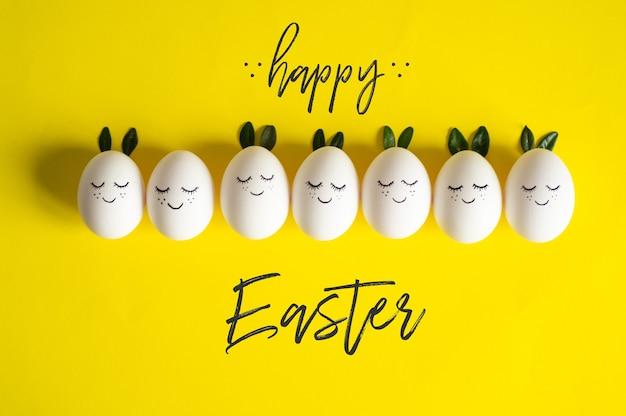 Wesołych świąt wielkanocnych. śliczne pisanki z pomalowaną twarzą wiosną pozostawia na żółtym tle. wesołych świąt wielkanocnych.