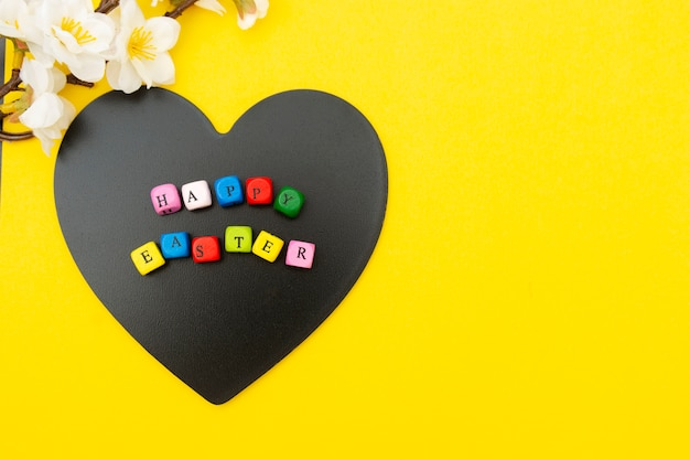 Wesołych świąt wielkanocnych. sześciany z tekstem na tablicy w kształcie serca, żółte tło. widok z góry, kompozycja wiosenna leżąca płasko.