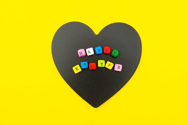 Wesołych świąt wielkanocnych. sześciany z tekstem na tablicy w kształcie serca, żółte tło. widok z góry, płasko ułożona kompozycja.