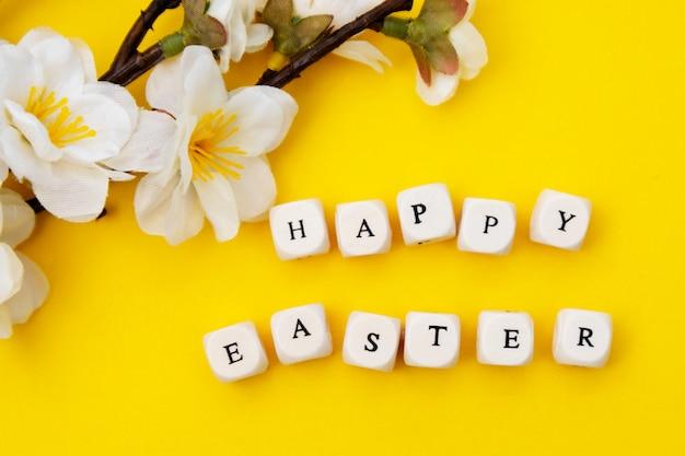 Wesołych świąt wielkanocnych. sześciany z tekstem na żółtym tle. wiosenne brunche z białymi kwiatami. minimalistyczne płaskie ułożenie.