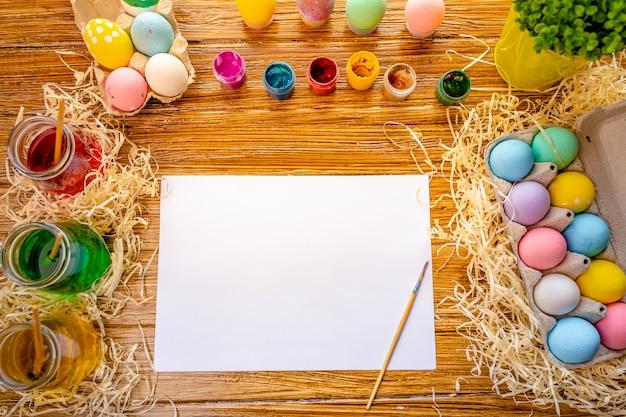Wesołych świąt wielkanocnych. tło z kolorowymi jajkami w koszu. dekorowanie stołu na wakacje. widok z góry.
