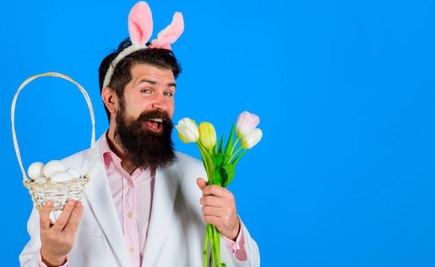 Wesołych świąt wielkanocnych. uśmiechnięty biznesmen w garniturze z koszem jajkiem i wiosennymi kwiatami. mężczyzna w uszach królika. polowanie na jajka.