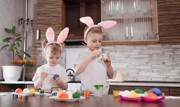 Wesołych świąt wielkanocnych. zabawne i szczęśliwe dzieci chłopiec i dziewczynka z uszami królika bawią się, przygotowują do wakacji i malują jajka.
