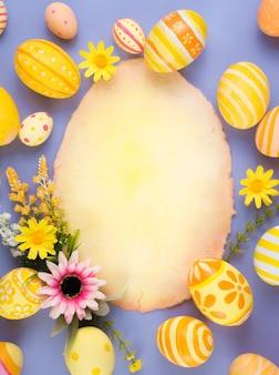 Wesołych świąt wielkanocnych żółte jajka i dekoracje kwiatowe na papierze