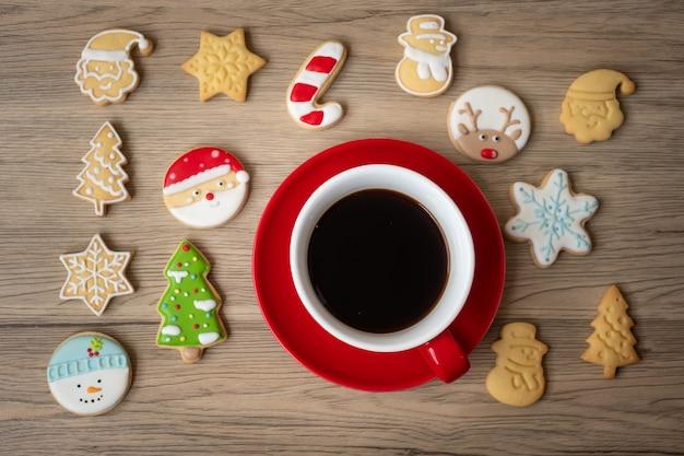 Wesołych świąt z domowymi ciasteczkami i filiżanką kawy na tle stołu z drewna. koncepcja wigilijna, imprezowa, świąteczna i szczęśliwego nowego roku