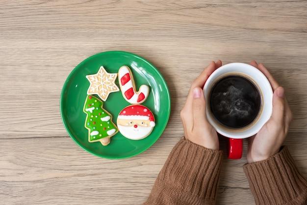 Wesołych świąt z kobieta ręka trzyma filiżankę kawy i domowe ciasteczka na stole. koncepcja wigilijna, imprezowa, świąteczna i szczęśliwego nowego roku
