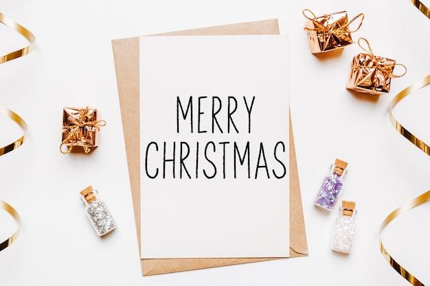 Wesołych świąt z kopertą, prezentami i złotymi gwiazdkami brokatu na białym tle. koncepcja wesołych świąt i nowego roku