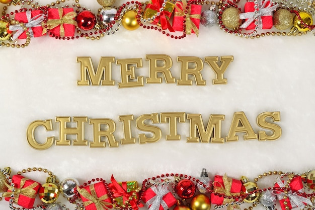 Wesołych świąt złoty tekst i ozdoby świąteczne na białym tle