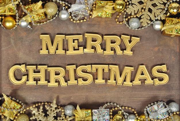 Wesołych świąt złoty tekst i ozdoby świąteczne na drewnianym tle