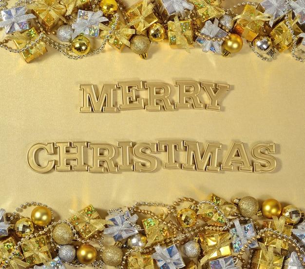 Wesołych świąt złoty tekst i ozdoby świąteczne na złotym tle