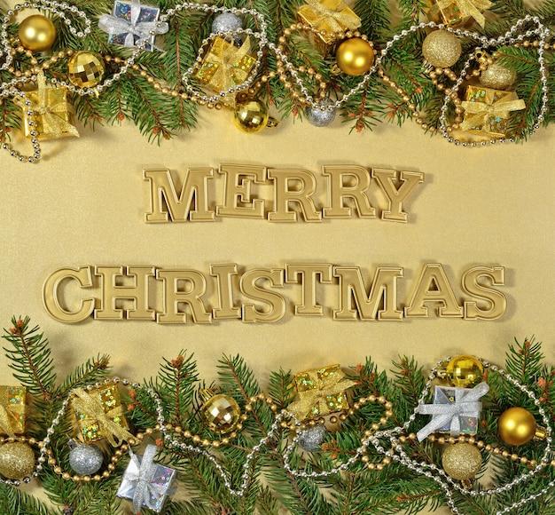 Wesołych świąt złoty tekst i świerkowa gałąź i ozdoby świąteczne na złotym tle