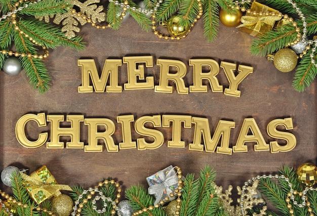 Wesołych świąt złoty tekst i świerkowa gałąź oraz ozdoby świąteczne na drewnianym tle
