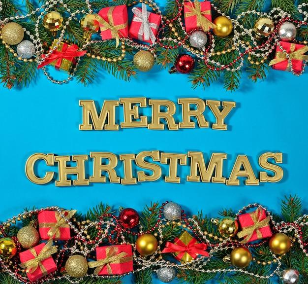 Wesołych świąt złoty tekst i świerkowa gałąź oraz ozdoby świąteczne na niebieskim tle