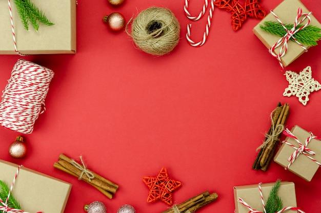 Wesołych świątecznych dekoracji. pudełko prezentowe i świerk z podstawowymi elementami leżącymi na różowym papierze na nowoczesnym czerwonym papierze