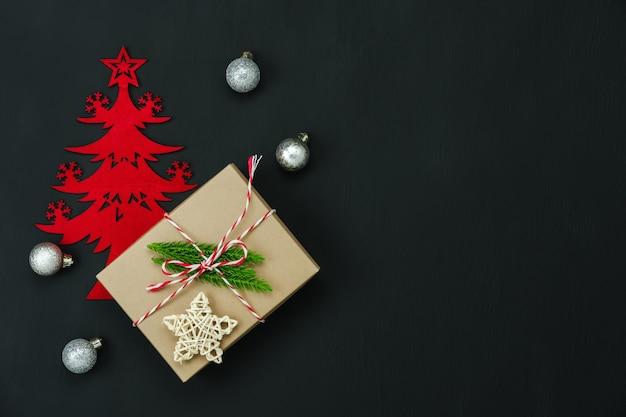 Wesołych świątecznych dekoracji. pudełko prezentowe i świerk z podstawowymi przedmiotami leżącymi na płasko na różowym papierze