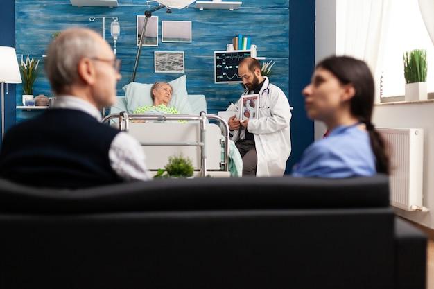 Wesprzyj lekarza pracownika wyjaśniającego radiografię serca omawiającą kardiogram medyczny