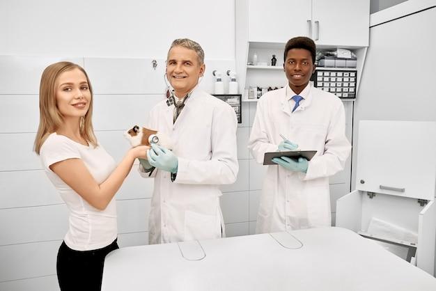 Weterynarz, asystentka i właścicielka chomika pozującego w klinice.