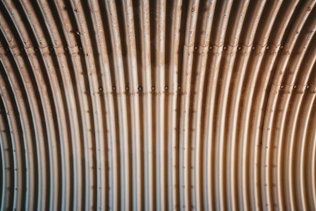 Wewnątrz duża tuba z symetrycznym pofałdowanym tłem, wykonana z metalicznego materiału