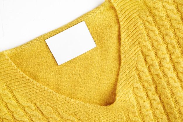 Wewnątrz metka z miejscem na kopię na szyi żółtego wełnianego swetra