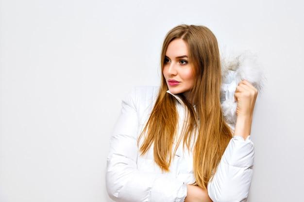 Wewnątrz moda portret młodej blondynki w białej zimowej kurtce, obraz z lampą błyskową, długie włosy, naturalny, makijaż, radość, zabawa.
