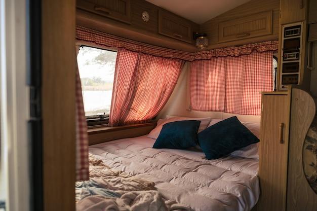 Wewnątrz nikogo samochód kempingowy z łóżkiem, poduszką, zasłoną na oknie na kempingu. zajęcia rekreacyjne na wakacjach
