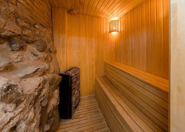 Wewnątrz nowoczesnej sauny, skalnej ściany i drewnianych ławek do siedzenia