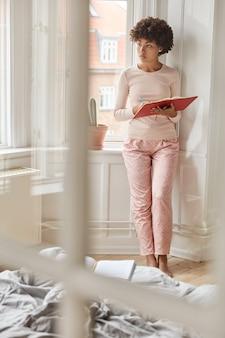 Wewnątrz, pionowe ujęcie na całej długości afroamerykanki w piżamie, pisze płyty w notatniku, stoi przy oknie, nagrywa pomysły na artykuł, pracuje w domu, marzy o czymś. wnętrze domu