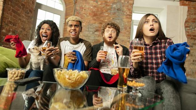 Wewnątrz. podekscytowani ludzie oglądają mecz, mistrzostwa w domu. wieloetniczna grupa przyjaciół, kibice dopingują ulubioną drużynę sportową
