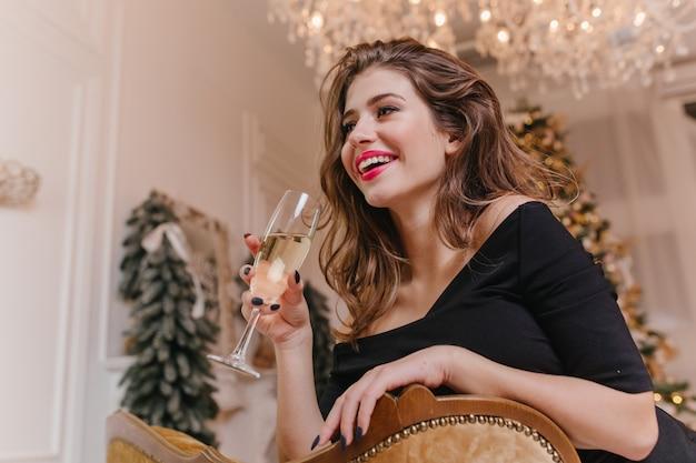 Wewnątrz portret fascynującej młodej kobiety w eleganckim stroju spędzającej czas w domu w zimowy dzień. kryty zdjęcie wesołej dziewczyny ze stylowym makijażem pije szampana w pokoju urządzonym na boże narodzenie.
