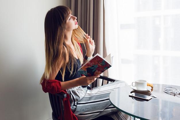 Wewnątrz portret ładna brunetka kobieta, czytanie książki, siedząc na krześle i pijąc kawę w słoneczny wiosenny poranek. pora śniadaniowa.
