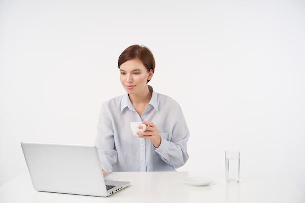 Wewnątrz portret ładnej młodej brunetki z przypadkową fryzurą pije filiżankę kawy podczas pracy na białym z nowoczesnym laptopem i uśmiecha się pozytywnie