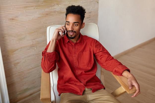 Wewnątrz portret młodego ciemnowłosego brodatego faceta wykonującego telefon podczas pracy w domu, siedzącego w wygodnym fotelu z telefonem komórkowym w uniesionej ręce