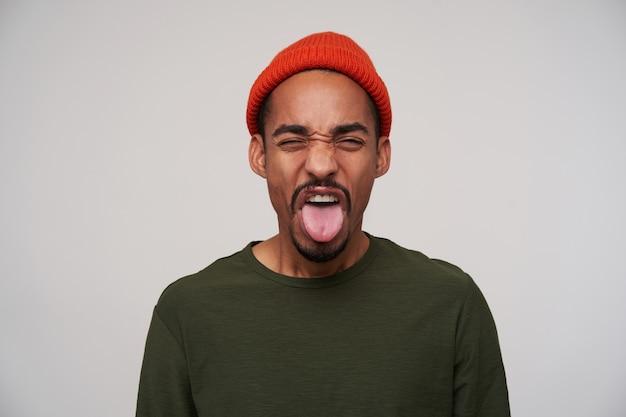 Wewnątrz portret młodego, dość brodatego ciemnoskórego faceta marszczącego brwi i pokazującego język, wyrażając obrzydzenie, stojącego na biało w codziennym noszeniu