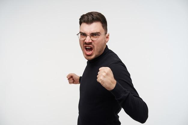 Wewnątrz portret młodego, wściekłego, krótkowłosego brodatego faceta, który skrzywił się na twarzy podczas pięści, ubrany w czarną poloneck, stojąc na białym