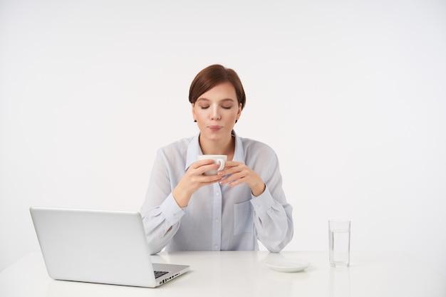 Wewnątrz portret młodej krótkowłosej brunetki kobiety z przypadkową fryzurą trzymającą filiżankę gorącej herbaty i dmuchającą na nią, ubraną w formalne ubrania, siedząc na białym