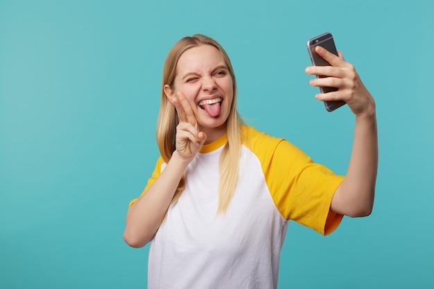Wewnątrz portret młodej ładnej blondynki długowłosej pani trzymającej rękę podniesioną podczas robienia selfie na telefonie komórkowym, śmiejąc się, pozując na niebiesko