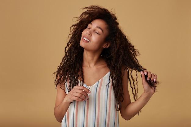 Wewnątrz portret młodej pozytywnie kręconej ciemnoskórej brunetki kobiety bawiącej się włosami i uśmiechającej się delikatnie z zamkniętymi oczami, pozując na beżu