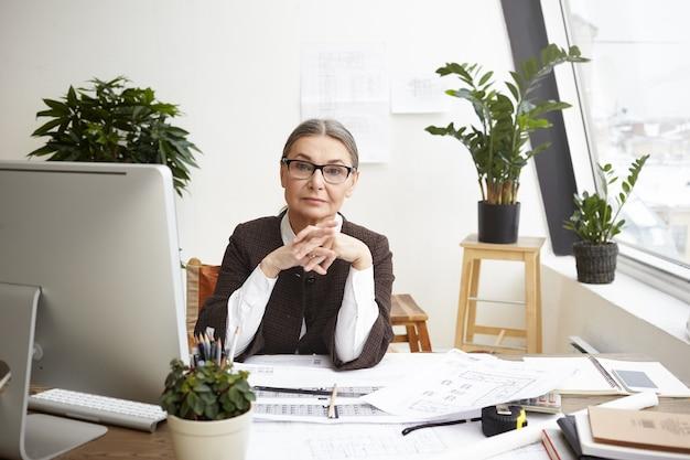 Wewnątrz portret poważnej profesjonalnej 55-letniej starszej architektki studiującej plany architektoniczne, sprawdzającej pomiary na komputerze i korygującej rysunki na biurku przed nią