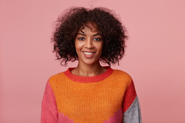 Wewnątrz portret pozytywnej, optymistycznej uroczej afroamerykanki z fryzurą afro wygląda z przyjemnością, z żywym uśmiechem, ubrana w kolorowy longsleeve, na białym tle