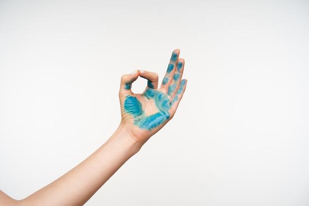 Wewnątrz portret ręki młodej damy pomalowany na niebiesko, tworząc znak namaste podczas pozowania na biało, medytując z uniesioną ręką