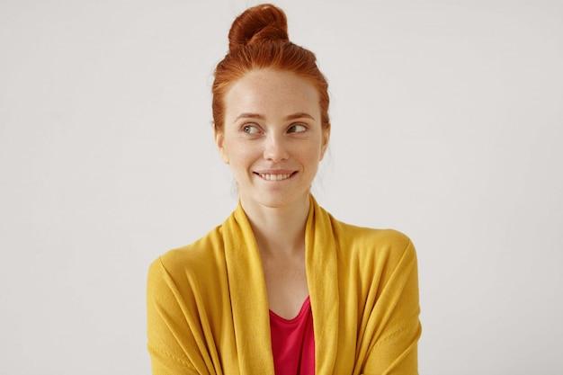 Wewnątrz portret tajemniczej uroczej młodej europejskiej kobiety gimger z węzłem włosów, patrzącej w bok z enigmatycznym uśmiechem