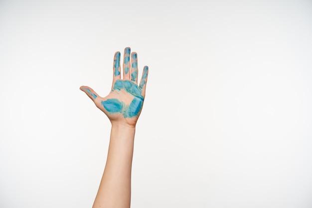 Wewnątrz portret uniesionego ramienia kobiety pokazujący dłoń pomalowaną na niebiesko podczas pozowania na biało. koncepcja języka ciała i gestów