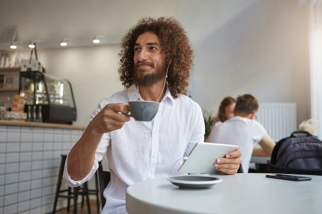 Wewnątrz portret uroczego młodego brodatego mężczyzny z brązowymi kręconymi włosami, podczas przerwy na lunch w kawiarni, picia kawy i słuchania muzyki, patrząc na bok ze szczerym uśmiechem