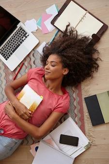 Wewnątrz portret uroczej ciemnoskórej kobiety z brązowymi kręconymi włosami odpoczywającej na podłodze po długim studiowaniu, trzymającej notatnik na piersi, zamykając oczy i uśmiechając się delikatnie