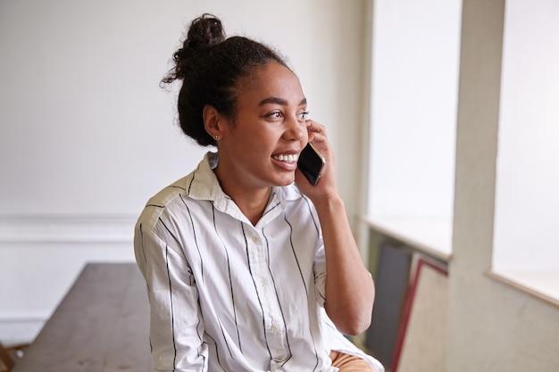 Wewnątrz portret uroczej szczęśliwej kobiety z telefonem komórkowym w dłoni, wyglądającej przez okno i szeroko uśmiechającej się, dzwoniącej do przyjaciela, w białej koszuli w paski
