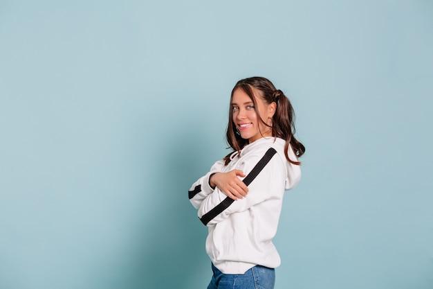 Wewnątrz portret uśmiechnięta ładna młoda kobieta o ciemnych włosach ubrana w biały sweter, pozowanie na odizolowanej ścianie